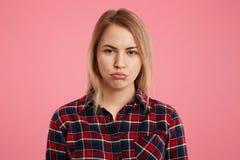 El modelo femenino abusado atractivo curva los labios como siendo ofendido por la persona cercana, expresa su descontento, aislad Imágenes de archivo libres de regalías