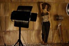 El modelo femenino afroamericano elegante en los accesorios del oro que se colocan y que presentan cerca de luz del estudio deste Imagen de archivo