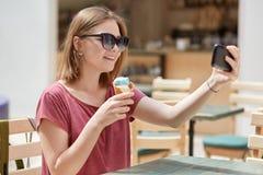 El modelo femenino alegre con sonrisa amistosa come el helado y hace el retrato del selfie en el teléfono celular, presenta en la fotografía de archivo libre de regalías