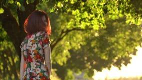 El modelo femenino atractivo da vuelta alrededor en luz de la puesta del sol en parque metrajes