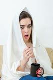 El modelo femenino cogió el frío cubierto con la manta blanca en casa Imagen de archivo