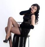 El modelo femenino en vestido de noche se está sentando Imágenes de archivo libres de regalías