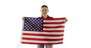 El modelo femenino es permanente y que sostiene la bandera americana en el fondo blanco almacen de video