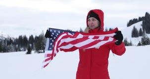 El modelo femenino joven está agitando la bandera americana de los E.E.U.U. encima de la montaña almacen de video