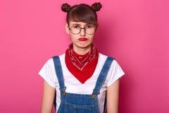 El modelo femenino joven trastornado parece offened, estando en mal humor, se coloca solamente y mira directamente la cámara, ha  imágenes de archivo libres de regalías