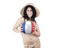 El modelo femenino sostiene la bola con una bandera de Francia Imagen de archivo libre de regalías