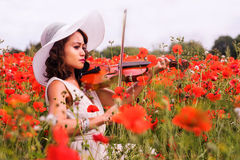 El modelo filipino toca el violín sorounded por las amapolas rojas imagen de archivo