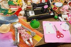 El modelo hecho a mano de la muñeca y de la ropa, accesorios de costura visión superior, lugar de trabajo de la costurera, muchos Fotos de archivo libres de regalías