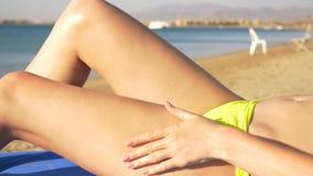 El modelo hermoso aplica una protección solar para las piernas HD almacen de metraje de vídeo