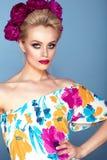 El modelo hermoso con el pelo del updo y brillantes perfectos componen el vestido abierto colorido del hombro que lleva con la gu Fotografía de archivo