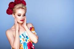 El modelo hermoso con el pelo del updo y brillantes perfectos componen el vestido abierto floral del hombro que lleva y la guirna Imagen de archivo