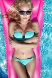 El modelo modelo hermoso con los pelos, las gafas de sol y el bikini mojados rubios largos nada en la piscina en un colchón rosad Foto de archivo libre de regalías