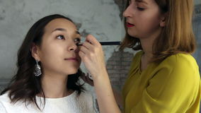 El modelo hermoso consigue un maquillaje profesional hecho por un vídeo estupendo del visagist metrajes