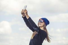 El modelo hermoso de la mujer con el teléfono contra el cielo hace selfi Foto de archivo