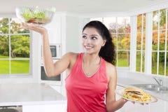 El modelo joven compara las comidas sanas y malsanas Fotos de archivo
