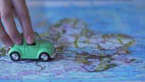El modelo móvil en mapa del mundo, viaje del coche de la mano humana alrededor de Europa, vacation en el extranjero almacen de video