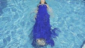 El modelo magnífico en vestido azul nada en piscina azul almacen de video