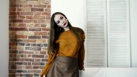 El modelo presenta al fotógrafo, muchacha con maquillaje oscuro en soportes de la ropa de moda cerca de la pared de ladrillo almacen de video
