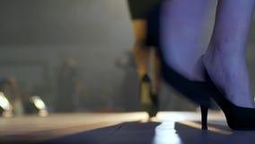 El modelo profesional en zapatos cómodos con el bolso en la mano va en el podio en la iluminación de lámparas almacen de metraje de vídeo