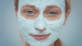 El modelo rubio en estudio hace una m?scara facial de limpiamiento almacen de metraje de vídeo