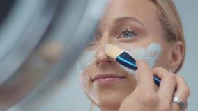 El modelo rubio en estudio hace una m?scara facial de limpiamiento metrajes