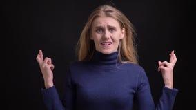 El modelo rubio joven en cruzar-fingeres azules de los gestos del suéter firma en la esperanza del éxito en fondo negro almacen de video