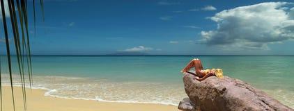 El modelo rubio tunning en roca de la playa. Panorama Imágenes de archivo libres de regalías