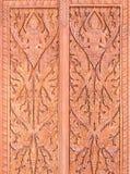 El modelo tailandés tradicional se talla en la puerta de madera roja Imagen de archivo libre de regalías