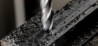 El molino de extremo del CNC de Bridgeport que acaba una pila de placa de acero con las limaduras del metal salta alrededor fotografía de archivo