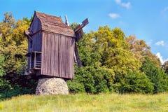 El molino de viento de madera ucraniano del molino de viento se coloca cerca de un bosque en la f Fotos de archivo libres de regalías