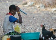 El molo woman makes chore. LAKE TURKANA, KENYA-JANUARY 12: El molo woman makes chore January 12, 2013 near lake Turkana, Kenya. The El molo are one of the stock photography