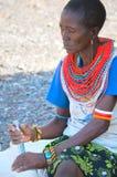 El molo woman makes chore. LAKE TURKANA, KENYA-JANUARY 12: El molo woman makes chore January 12, 2013 near lake Turkana, Kenya. The El molo are one of the royalty free stock image