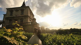 El momento romántico de pares del recién casado en puesta del sol parquea cerca del edificio del palacio del vintage metrajes