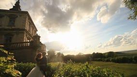 El momento sensual de pares románticos del recién casado en puesta del sol parquea cerca de las paredes del palacio del vintage almacen de metraje de vídeo