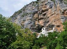 El monasterio construido dentro de la roca y de los árboles debajo del monasterio de Ostrog - valle de Bjelopavlici imagen de archivo libre de regalías