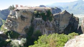 El monasterio se encaramó arriba para arriba en las rocas en Meteora, Grecia con Mountain View más allá Imágenes de archivo libres de regalías