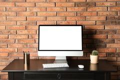 El monitor de computadora moderno en la pared de ladrillo del escritorio, imita para arriba con el espacio para el texto fotografía de archivo libre de regalías