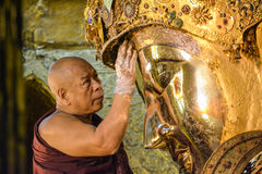 El monje birmano no identificado está limpiando la estatua de Buda con el papel de oro en el templo de Mahamuni Buda, agosto Imagen de archivo