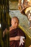 El monje birmano no identificado está limpiando la estatua de Buda con el papel de oro en el templo de Mahamuni Buda, agosto Imagenes de archivo
