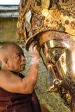 El monje birmano no identificado está limpiando la estatua de Buda con el papel de oro en el templo de Mahamuni Buda, agosto Fotos de archivo libres de regalías