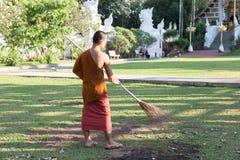 el monje budista que trabaja con la escoba barre el césped de las hojas caidas Fotos de archivo libres de regalías