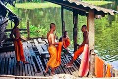 El monje budista vierte el agua en el lago sap de Tonle Imagen de archivo libre de regalías