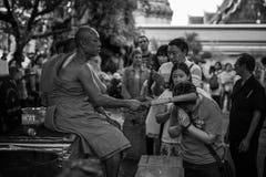 el monje da el agua santa a la gente Foto de archivo libre de regalías