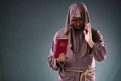 El monje en concepto religioso en fondo gris Imagenes de archivo