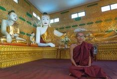 El monje indefinido medita en el Shwethalyaung Buda el 6 de enero de 2011 Foto de archivo