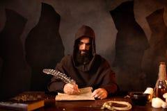 El monje medieval hace notas con una pluma del ganso imagenes de archivo