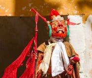 El monje no identificado en máscara con la lanza realiza danza religiosa del misterio del budismo tibetano durante el festival de imagenes de archivo