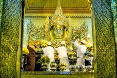 El monje realiza el ritual diario de lavar la cara de Maha Muni Sacred Living Image en la madrugada en Mandalay, M imagen de archivo libre de regalías