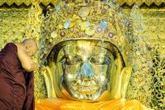 El monje realiza el ritual diario de lavar la cara de Maha Muni Sacred Living Image en la madrugada en Mandalay, Myanmar foto de archivo