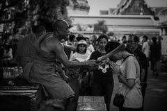 El monje tailandés da el agua santa a la gente Imagenes de archivo